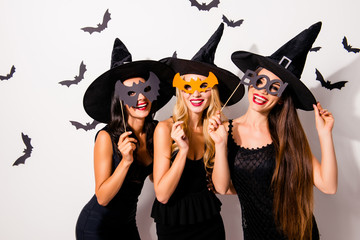 Group of three diverse charming coquettes in dark masquerade elegant dresses, masks on eyes, smiling, enjoying near decorated wall with bats, toothy beaming smiles, scary bright cosmetics hot figures Wall mural