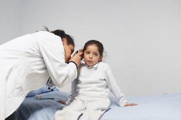 Female doctor check girl's ears