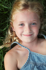 Content Little Blonde Girl Laying in Grass Smiling