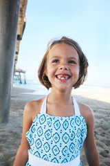 Girl With Missing Teeth Smiling Big At Beach