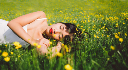 Beautiful young asian woman sleeping in the spring field with yellow flower under the sun