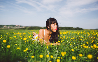 Beautiful young asian woman relaxing on the spring field