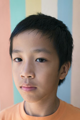 Portrait of a thoughtful young 9 year old boy against a pastel background