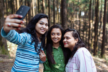 Group of friends taking selfie in the forest