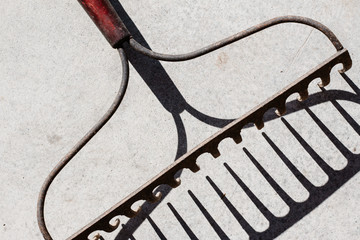 Close up of garden rake and shadow on concrete floor
