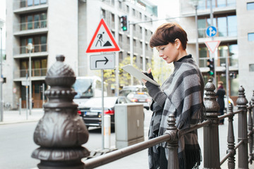 Outdoor City Portrait of Pretty Caucasian Woman Touching Digital Tablet With Index Finger