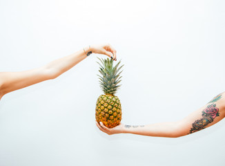 Two arms holding a pineapple