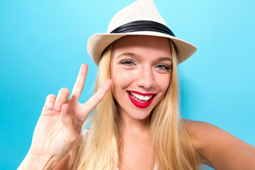 Young woman taking a selfie on a solid background