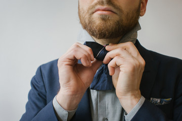 Men's Fashion - Close Up of Blond Caucasian Man Tying Bow Tie
