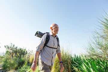 Senior man hiking on a mountain trail in a sunny day.