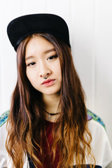 Asian girl with septum in cap looking at camera