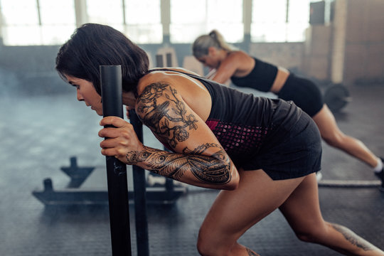 Fit young woman pushing prowler sled at gym