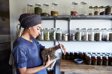 Millennial African American Woman Maker in Her Studio Looking at ingredients