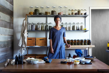 Herbalist stands in front of ingredients in her workshop
