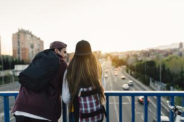 Happy Teen Couple Having a Walk Through a Bridge