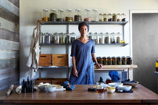 Herbalist stands in front of ingredients in her workshop