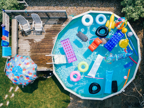Overhead drone image of an above ground pool filled with pool floats