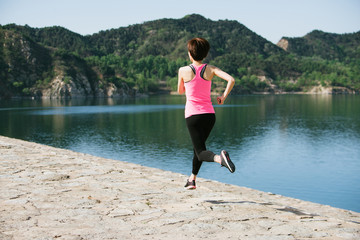 Young woman running besides a lake