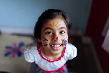 Little girl with a face paint having fun