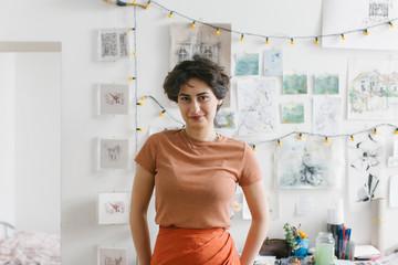 Indoor Portrait of Mixed Race Female Painter in Front of Artwork