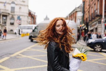 Young Beautiful Girl On the Street Holding Sunflowers