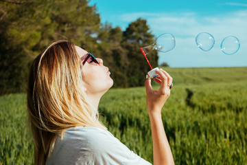 Portrait of young woman blowing bubbles