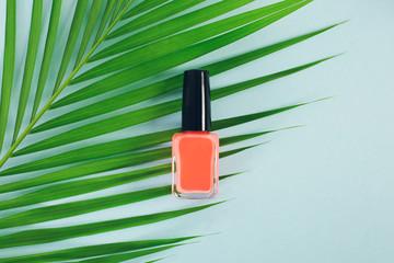 Orange nail polish bottle from above.