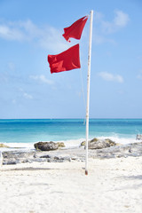 Tropical beach with red warning flag