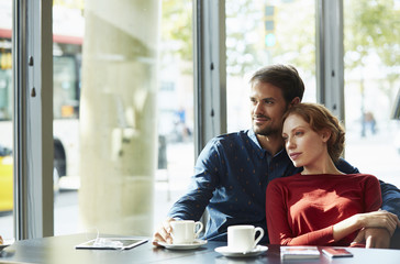 Loving Couple Looking Away While Sitting In Restaurant