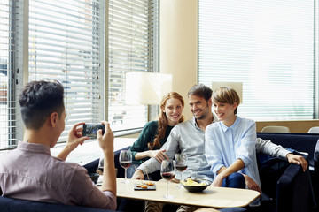 Man Photographing Friends In Restaurant
