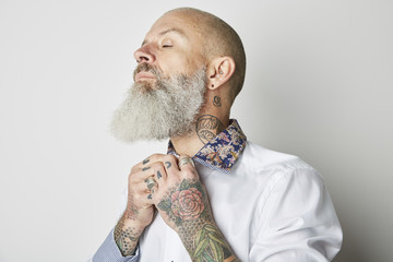 Studio portrait of man with tattoos fixing collar