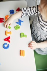 Little toddler girl playing with coloured letters