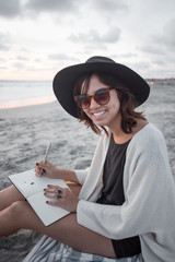 Pretty girl smiling with sunglasses writing in her notebook at the beach in the summer