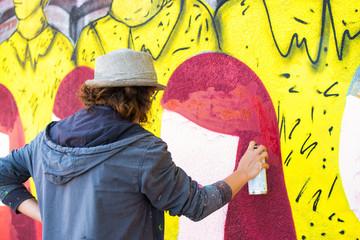 Female graffiti artist writing on wall