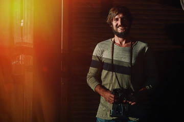 Smiling bearded guy with a camera posing in sunlight