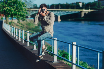 Young Fashionable man takes a photo with an old retro camera in the park