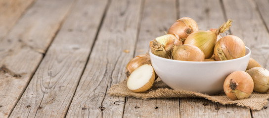 Wooden table with White Onions, selective focus
