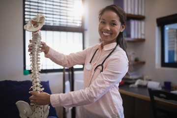 Portrait of smiling young female therapist examining artificial