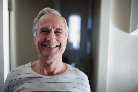 Close-up portrait of smiling senior male patient standing in
