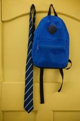 Schoolbag and tie hanging on door