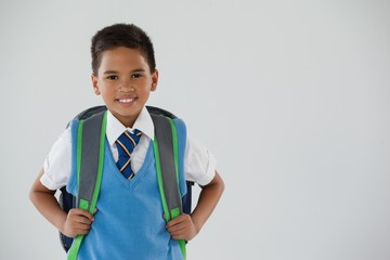 Schoolboy in school uniform with school bag on white background