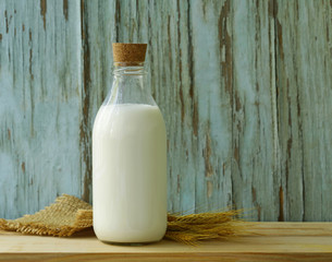 Organic milk in a glass bottle on a wooden table