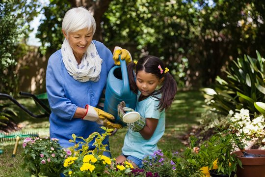 Smiling grandmother and granddaughter watering plants