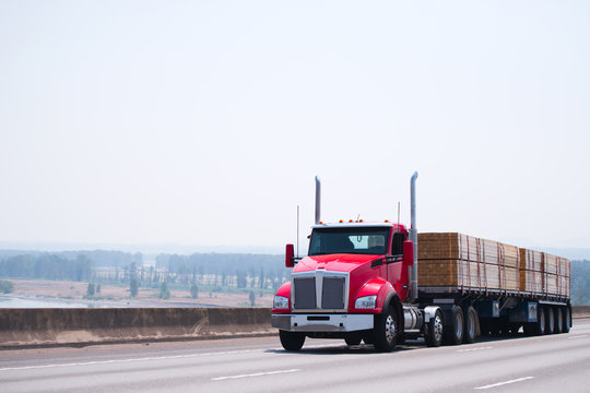 Big rig day cab red semi truck with flat bed trailer transporting lumber wood by wide multiline highway