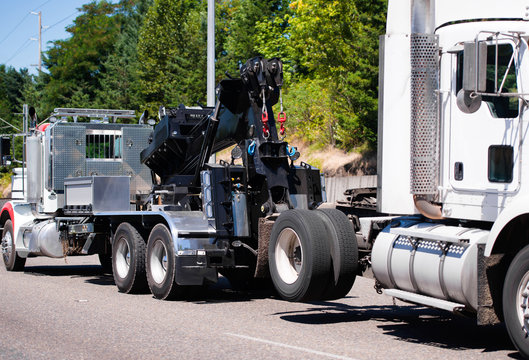 Big rig towing semi truck tow ather semi truck tractor on the road