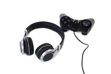 Joystick and headphones on white background