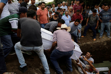 People lower casket of earthquake victim into grave, in Atzala