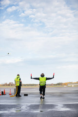 Marshaller Holding Signal Wands While Standing By Colleague On R