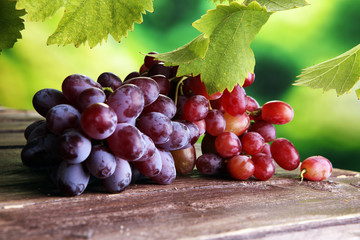 Grapes on wooden table and grape leaves . Healthy fresh fruit wine grapes. Fototapete