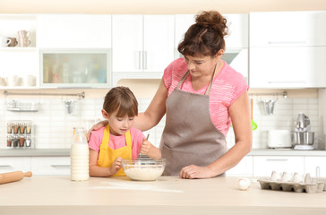 Cute little girl and her grandmother making dough on kitchen